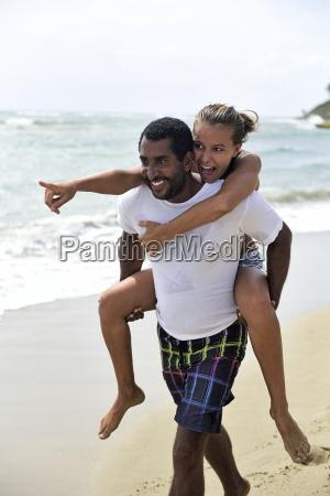 mann geben freundin huckepack am strand