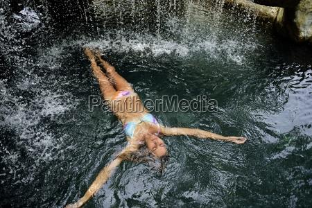 junge frau schwimmt im wasser im