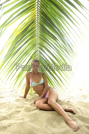 beautiful young woman sitting under palm