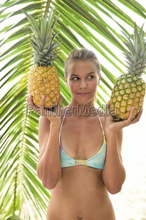 junge frau haelt zwei ananas an
