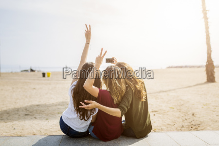 rueckansicht von drei freundinnen am strand