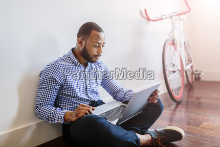 man using laptop sitting on wooden