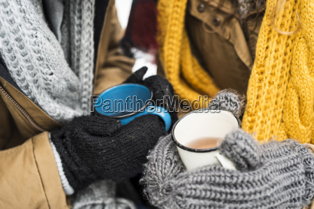 young couple wearing gloves holding cups