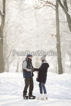 senior couple with ice skates standing