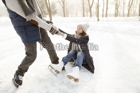 man helping ice skating woman getting
