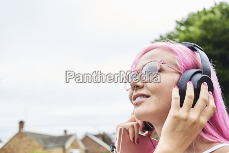 young woman with pink hair listening