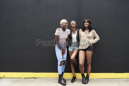 three friends standing against black background