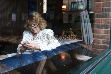 senior businesswoman checking cell phone in