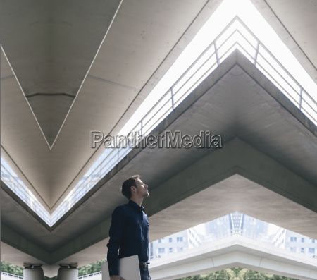 businessman standing at underpass holding laptop