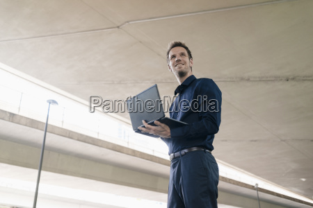 confident businessman standing at underpass using