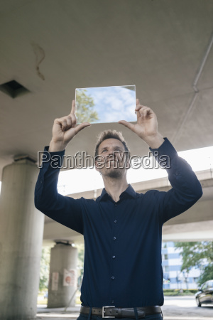 smiling businessman holding up portable glass