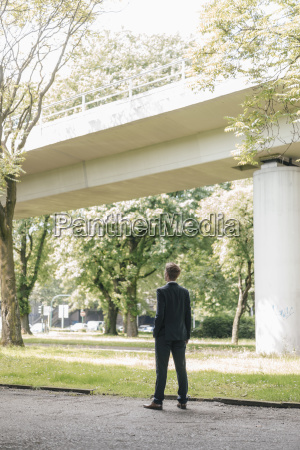 businessman standing outdoors at a bridge