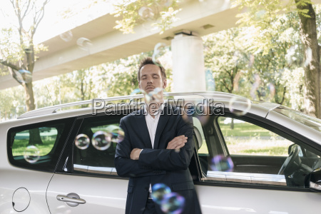 businessman standing next to car surrounded