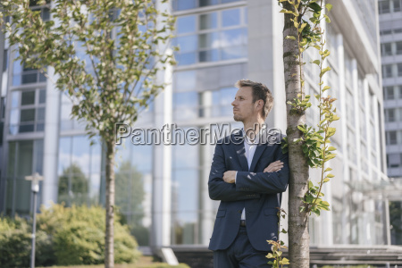 businessman leaning against a tree in
