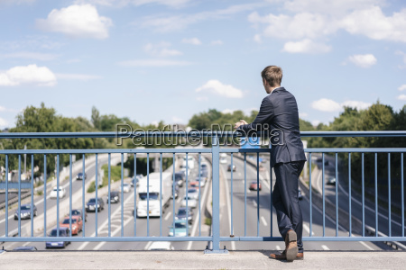 businessman standing on a bridge over