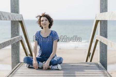 portrait of woman sitting on boardwalk