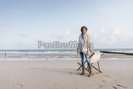 woman standing next to deckchair on