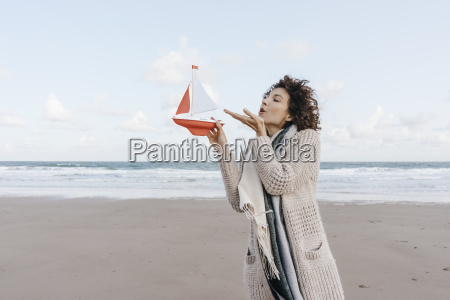 woman blowing at toy boat on