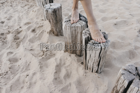 womans feet walking on wooden stakes