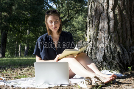 young woman sitting under a tree