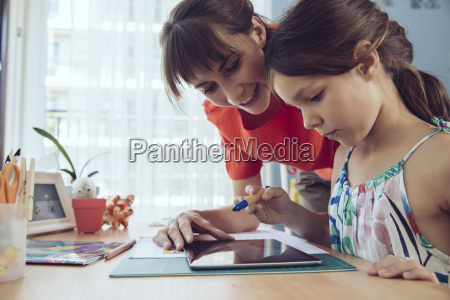 mother and daughter using tablet at