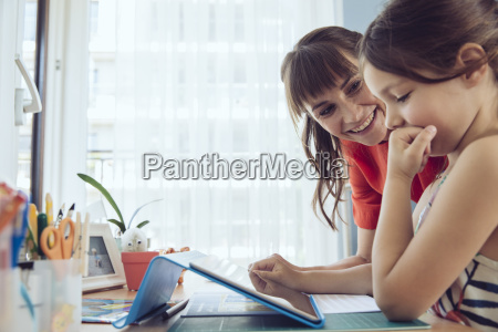 mother looking at daughter using tablet