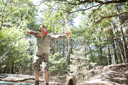 man shooting with bow and arrow