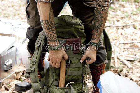 mann mit axt und rucksack im