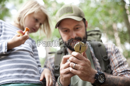 father showing compass to daughter in