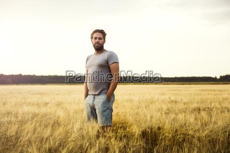 mann steht im getreidefeld