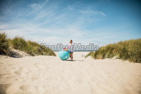 maedchen mit globus am strand