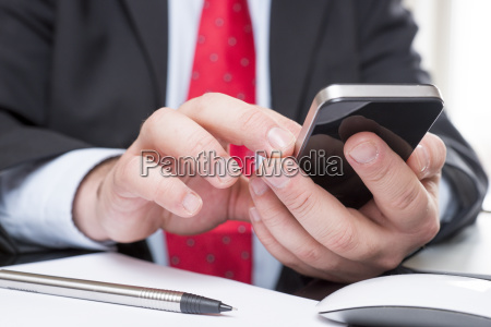 businessman sitting at desk text messaging