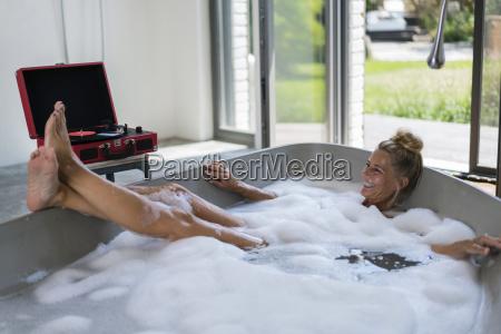 mature woman taking bubble bath listening