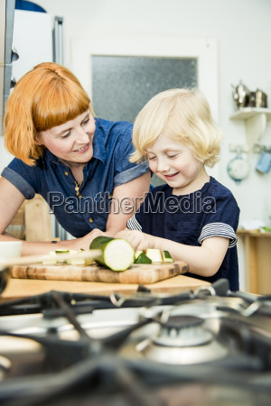 littel boy chopping vegetables in the