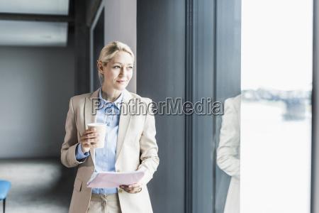geschaeftsfrau mit kaffee und dokumenten am