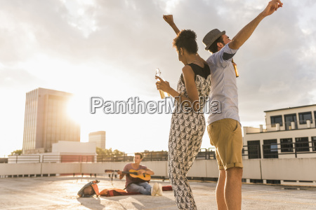 young couple dancing on a rooftop