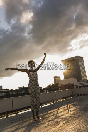 young woman with headphones dancing on