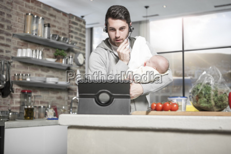 father with headset and tablet in