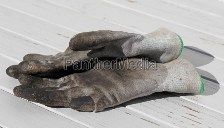 dirty work gloves on white wooden
