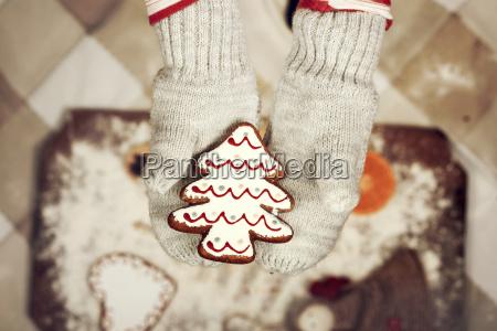 kinderhaende in handschuhen mit lebkuchen cookie