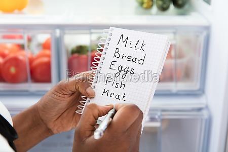 woman writing on shopping list near