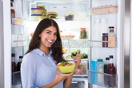 glueckliche frau die gemuesesalat isst
