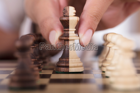 person hand playing chess and holding