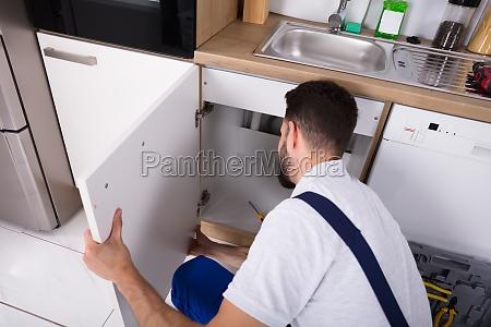 handyman fixing sink door