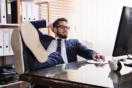 entspannter geschaeftsmann arbeitet am computer