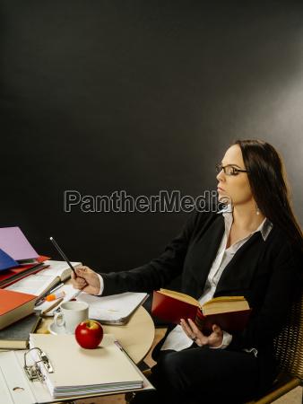 frau sitzt an ihrem schreibtisch schreiben
