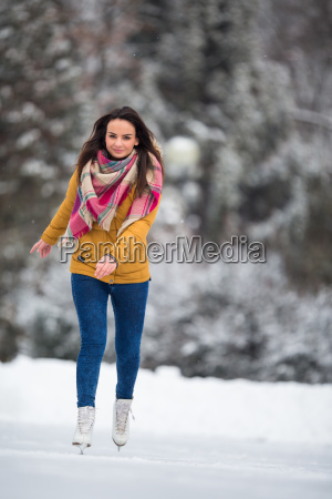 young woman ice skating outdoors on