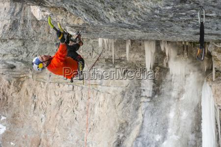 man upside down while ice climbing