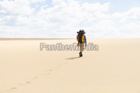 woman hiking on sandy beach in