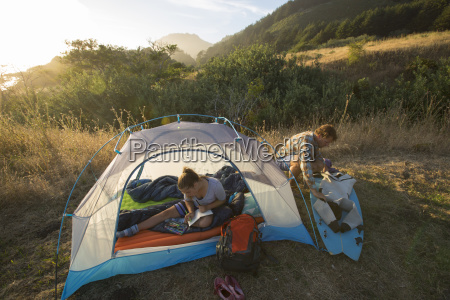 father and daughter camping in tent